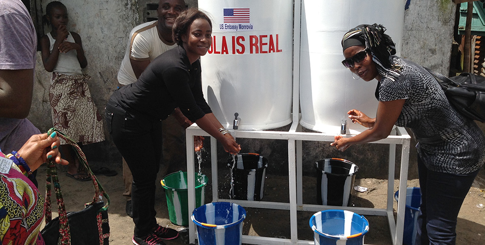 Photo: Sarah's (left) project provides stationary hand-washing tanks in the densely populated community of West Point.